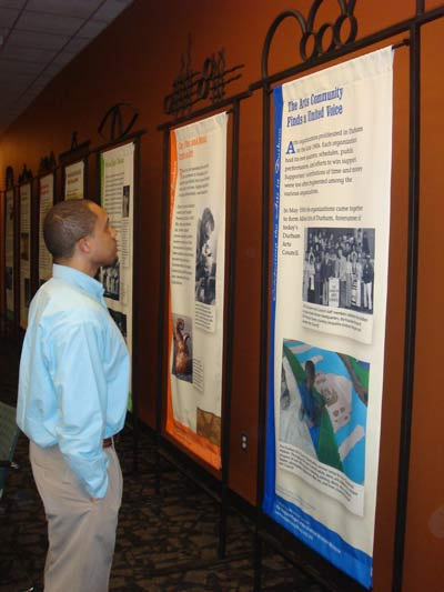 Photo Caption: William Evans learns more about Durham's art history on the banner exhibit featured at Durham Tech.