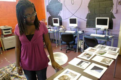 During the run-up to this summer's photo exhibit at SeeSaw Studio, Zenzele Barnes goes over the choices. (Photo by Alex Nelson)