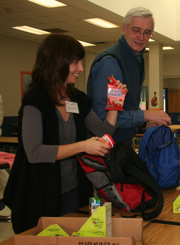 Elizabeth Levene of Communities In Schools and Ted Compton, a CIS volunteer,  load backpacks with food to carry students through the weekend.