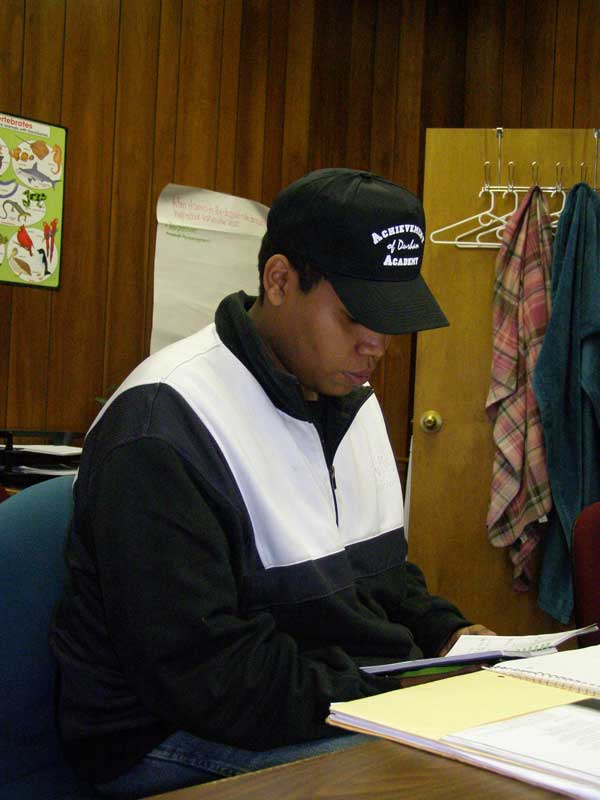 "Jason Smith begins to do his Friday homework for Durham Technical Community College. He is wearing his Achievement Academy hat, a privilege the staff awards to ""graduates and heroes."""