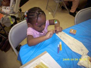 Katelyn McNeil,3 coloring a skeleton at the Arts and Crafts center during the Hallelujah Carnival