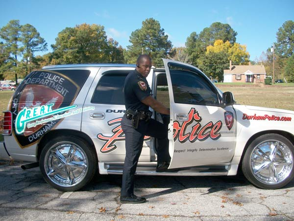 Durham Police Officer Larry Watkins shows off a Cadillac Escalade that is used as a teaching tool in GREAT, the Gang Resistance Education & Training Program.