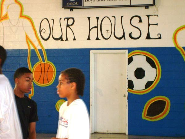 Members of the Boys and Girls Club take a break from homework in the school's gym. The message on the wall illustrates the attachment many members feel toward the club. Photo by Katie Little.