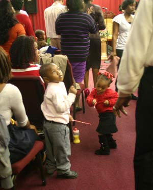 Two young children join in on worship and praise. Photo by Corliss Pauling.