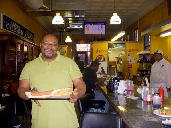 Diner owner Joseph Bushfan presents one of his diner's famous one-pound hot dogs. The hot dog takes two buns to eat and has been popular among customers.