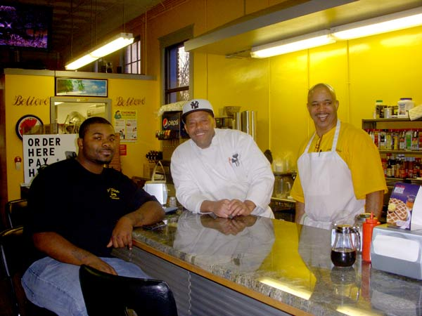 Macklin Bushfan, an employee and son of Joseph, sits at the counter (left) with chefs Bobby Wade (center) and Danny Graham (right). Photo by Lindsay Ruebens.