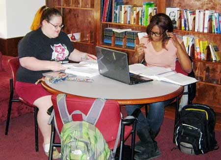Studying in comfy residential hall libraries is only one aspect of campus life early college students have to look forward to, said NCCU hospitality and tourism major Taylor McKracken (left) and biology major Kyra Lyles. (Staff photo by Marcus Christon)
