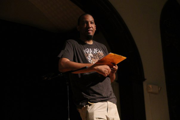 Dasan Ahanu, the founder and host of the Soul Slam, takes score of a poet's performance. (Photo courtesy of Dasan Ahanu).