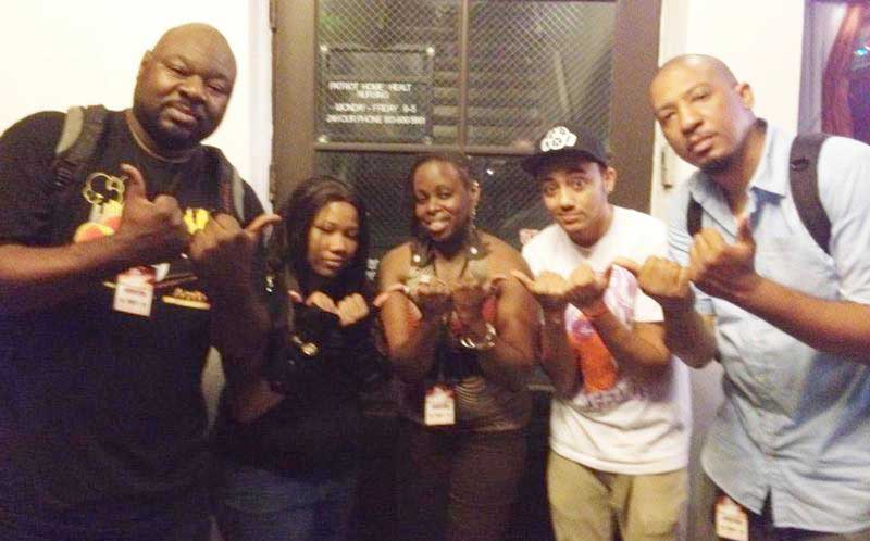 "The 2012 Bull City slam team throws up the ""bull horns"" hand gesture. From left: Elliot Axiom, SLAP, Kimberly ""Redefining Freedom"" McCrae, Ishine, Dasan Ahanu. (Photo courtesy of Dasan Ahanu)."