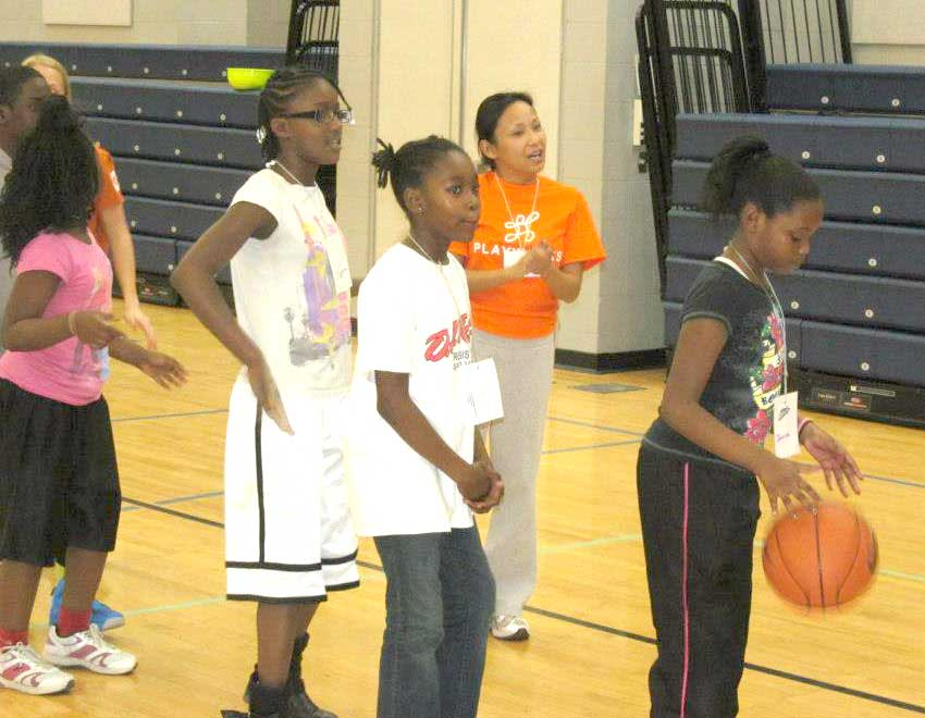 Playworks volunteer Genevieve Flores cheering on her basketball players at the Emily K Center. (Playworks)