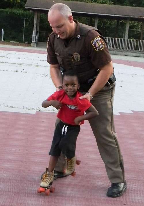 Durham County Sherrifs Deputy John Shelton assists a young skater around the rink. (Staff photo by Claire Queally)