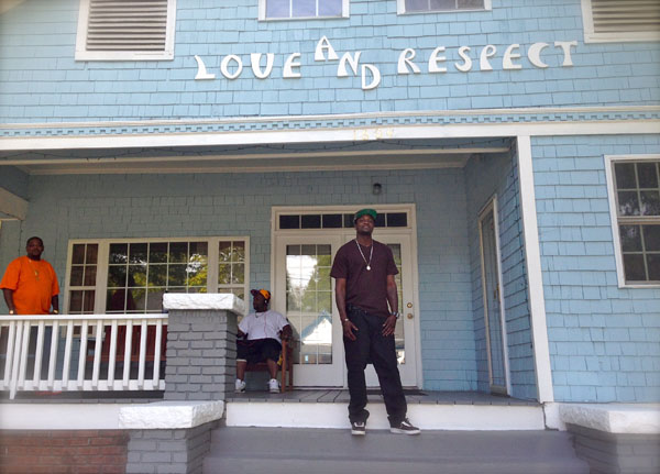 Willie Johnston stands on the steps of Love and Respect with a smile on his face, as Dennis Garrett, owner and founder, on the far left hand side looks on.  Another resident of the house sits, and listens to his music. (Staff photo by Sheila Rosier)