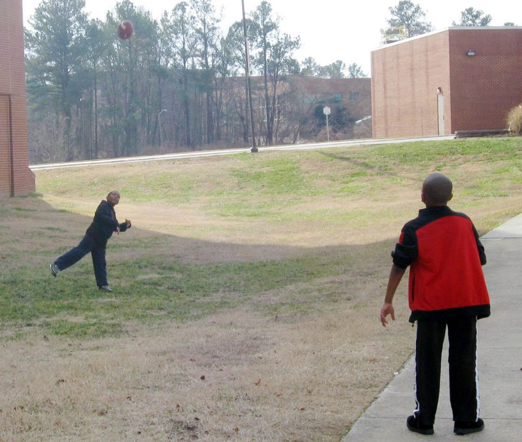 Outside the gym, boys toss around their new football – a holiday tradition.