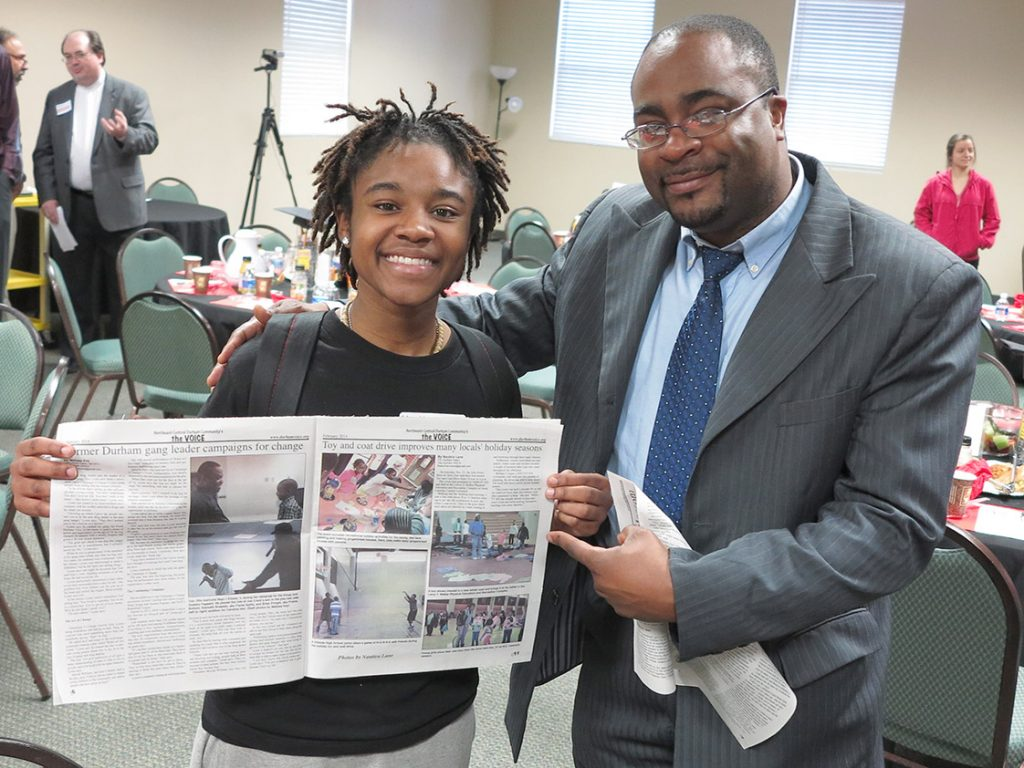 YO: Durham intern Nautica Lane grins as she sees her story-photo spread for the first time in the Durham VOICE, as Teen Mentoring Coordinator Carlton Koonce looks on proudly. (Staff photo by Jock Lauterer)